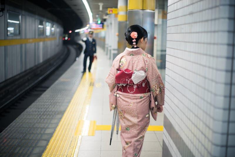 Kvinnahandelsresande i kimonoklänning på gångtunnelstationen royaltyfri fotografi