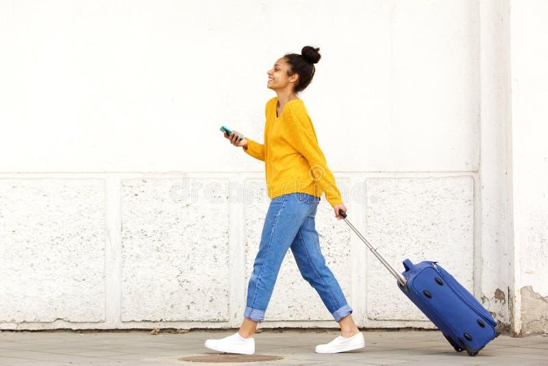Kvinnahandelsresande med bagage och mobiltelefonen arkivfoto