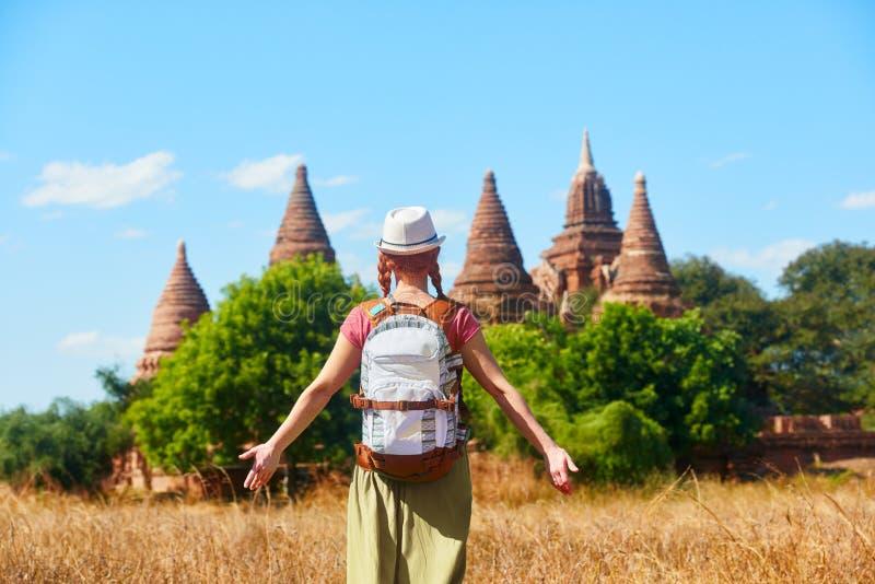 Kvinnahandelsresande med en ryggsäck som går till och med fält till forntida stupas arkivfoton