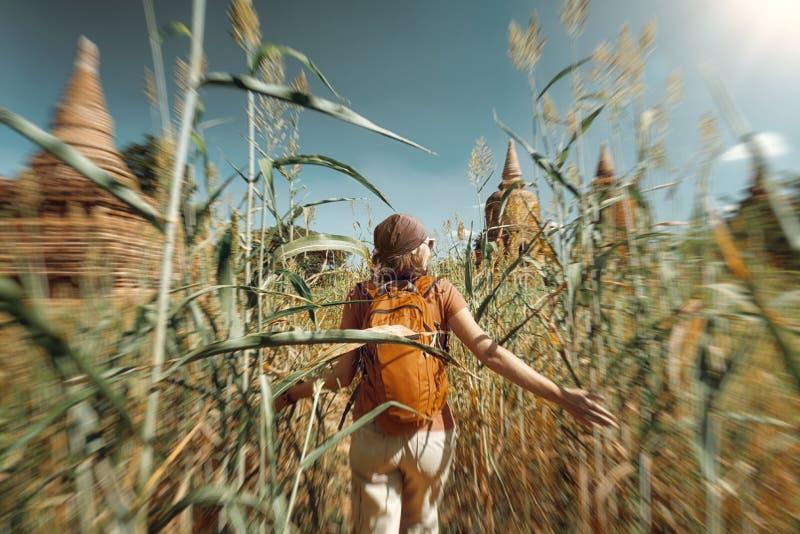 Kvinnahandelsresande med en ryggsäckkörning till och med fält till forntida stup arkivfoto
