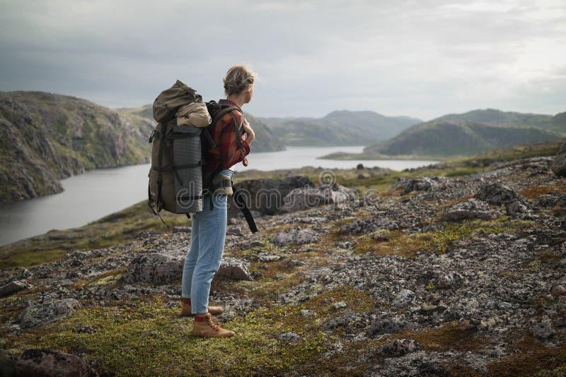 Kvinnahandelsresande med ryggsäcken som fotvandrar i berg arkivfoton