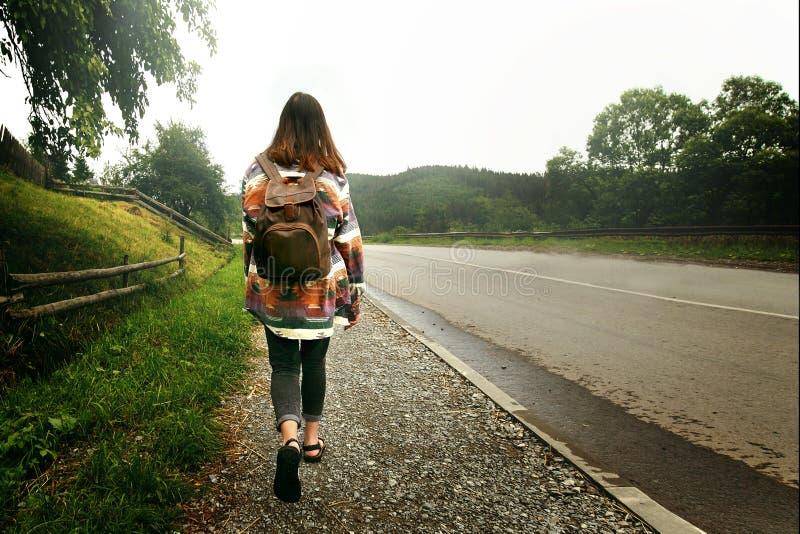 Kvinnahandelsresande med ryggsäcken som går ner vägen i berg, royaltyfria foton