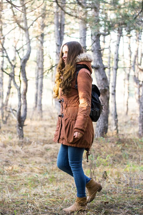 Kvinnahandelsresande med ryggsäcken som ser förbluffa skogen, reslustloppbegrepp, atmosfäriskt ögonblick arkivbild