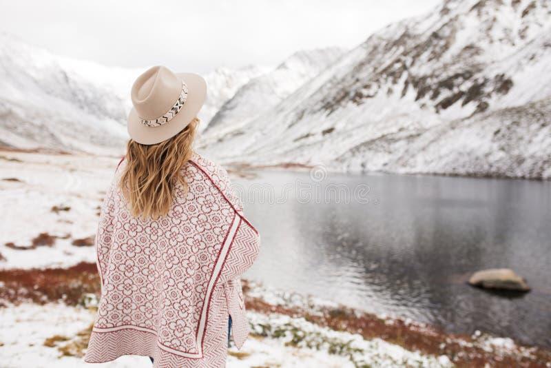 Kvinnahandelsresande på bakgrunden av en bergsjö arkivfoton