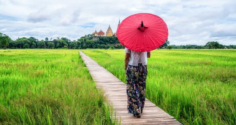 Kvinnahandelsresande som fotvandrar asiatiskt risf?ltlandskap arkivbild