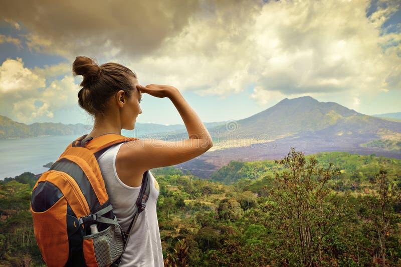 Kvinnahandelsresande som ser den Batur vulkan  arkivfoton