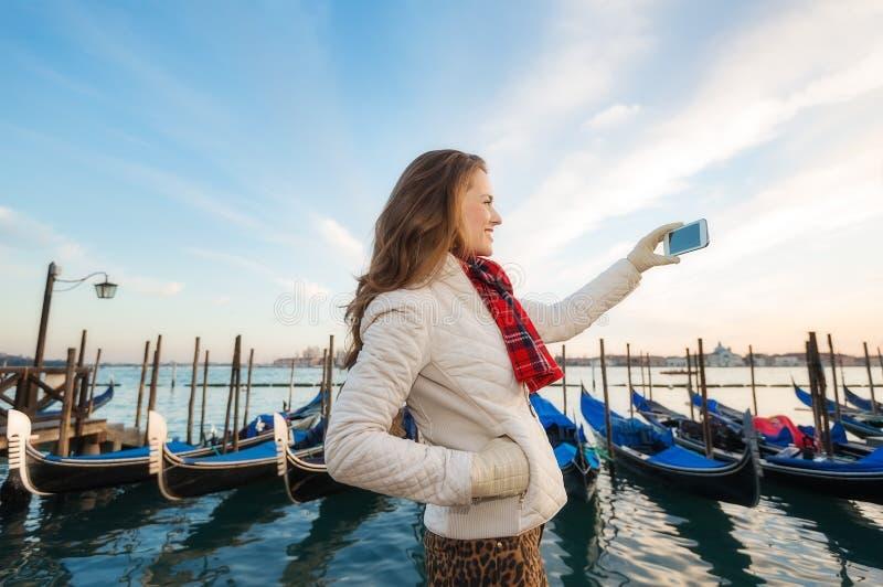 Kvinnahandelsresande som tar foto på invallning i Venedig, Italien royaltyfri foto