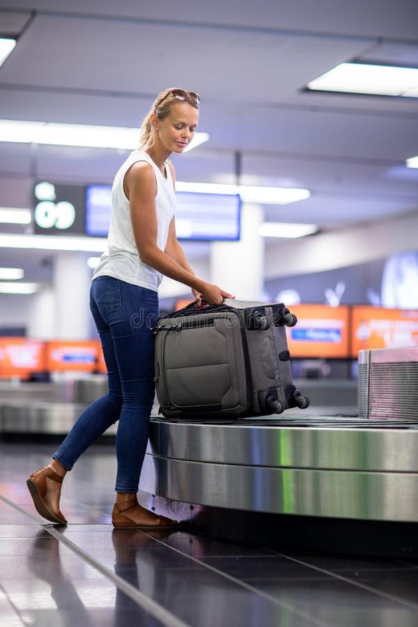 Kvinnahandelsresande som upp väljer resväskan från bagagereklamation royaltyfria foton