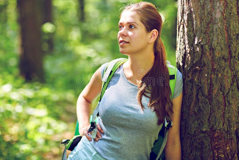 Kvinnahandelsresandeanseende i skog nära stort träd royaltyfria foton