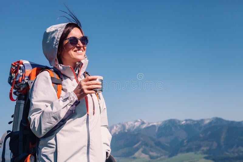 Kvinnahandelsresanden dricker te på bergöverkanten arkivbilder