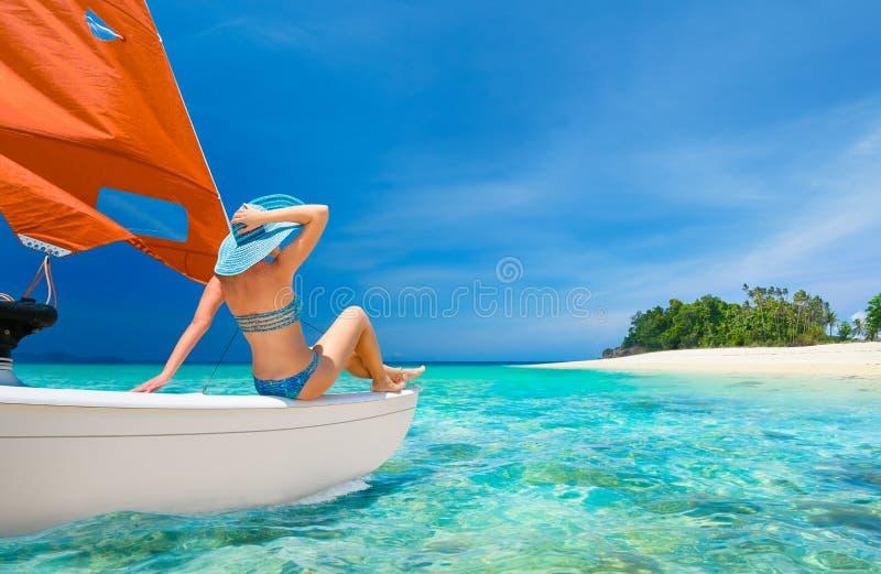 Kvinnahandelsresanden sitter på aktern av segelbåten som ser till stranden arkivfoto