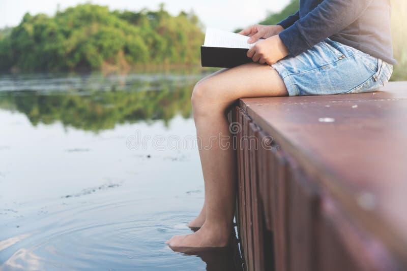Kvinnahandelsresandesammanträde och läsebok på floden och den gröna monteringen royaltyfri bild