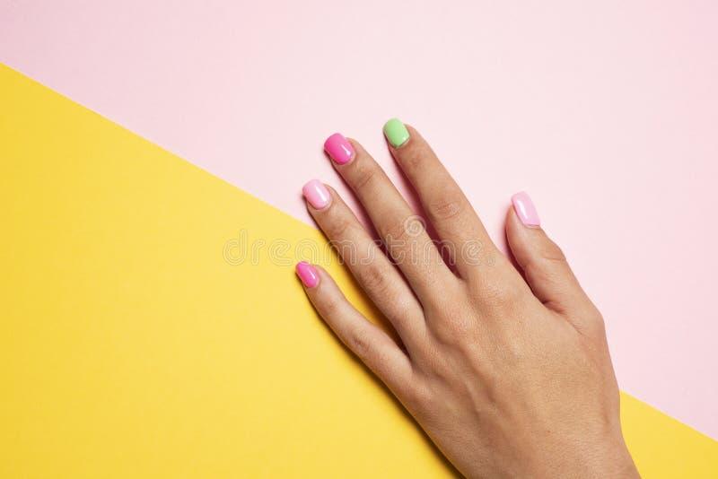 Kvinnahanden med henne spikar målad rosa färger och gräsplan royaltyfri fotografi