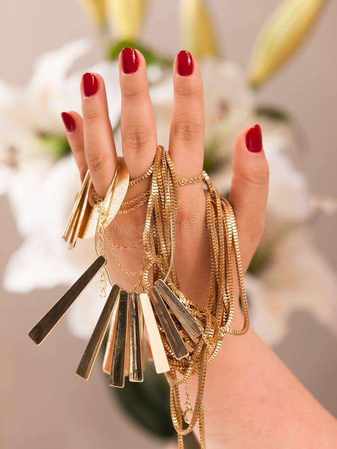 Kvinnahanden med rött spikar och guldjuvlar royaltyfri foto