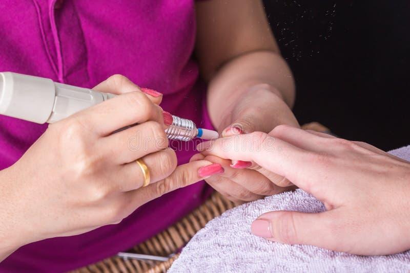 Kvinnahanden, medan processen av manikyr spikar in, shoppar Härligt lura royaltyfria bilder