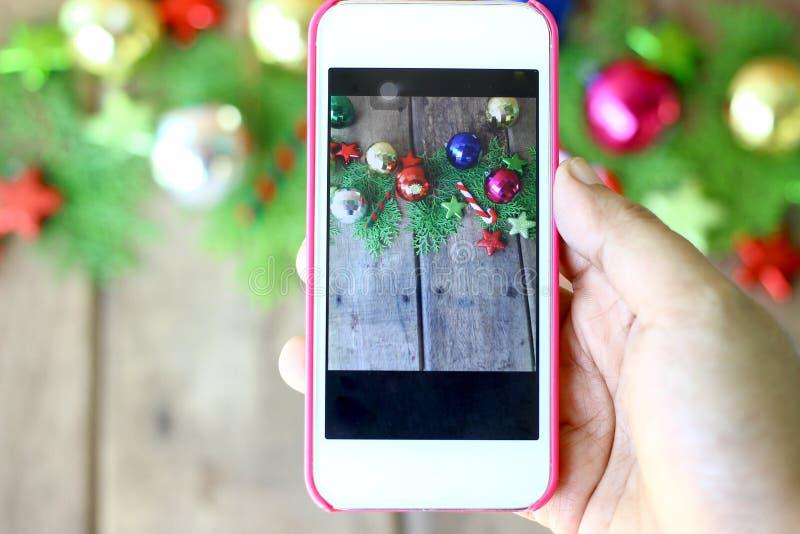 Kvinnahanden rymmer telefonen för att ta foto av julpynt arkivbild
