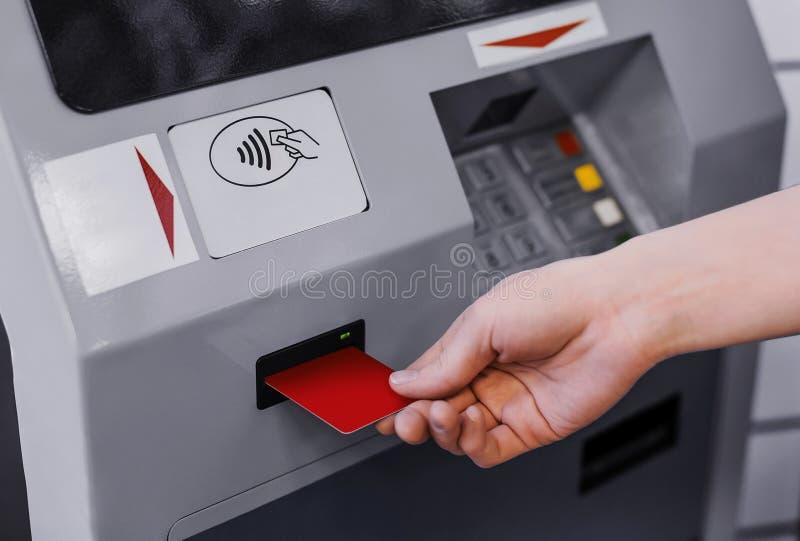 Kvinnahanden satte kreditkorten in i ATM arkivfoton