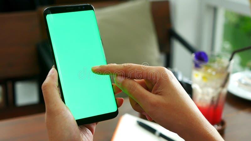 Kvinnahanden som rymmer den mobila smarta telefonen med den tomma gröna skärmen, bruksfingerglidbana på den gröna skärmen på kafé royaltyfri bild