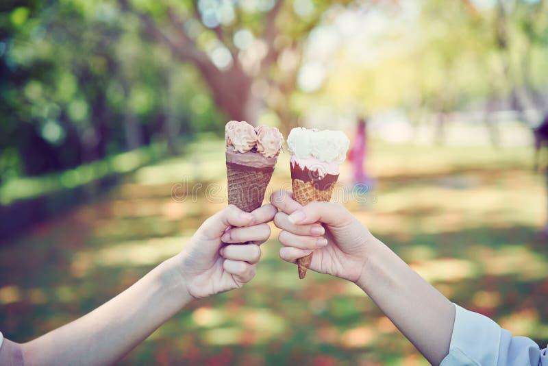 Kvinnahanden som rymmer en glass, kolliderar och lyckligt tiden av avkoppling arkivfoton