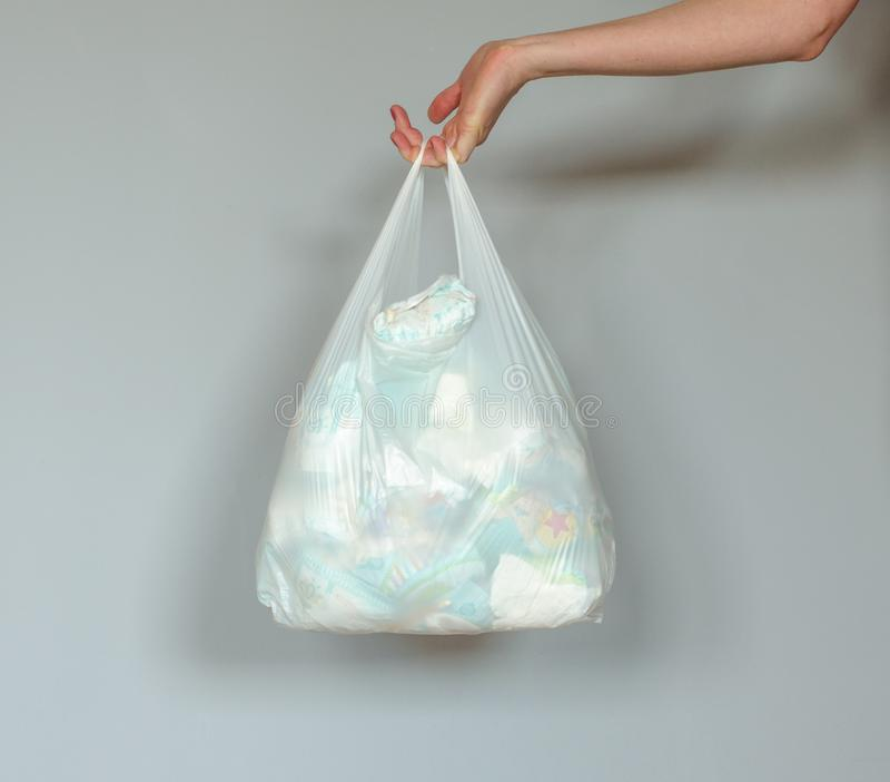 Kvinnahanden som rymmer en plastpåse full av använt smutsigt, behandla som ett barn blöjor royaltyfri fotografi