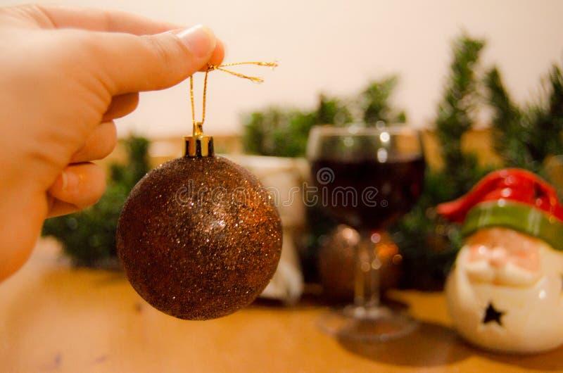 Kvinnahanden som rymmer jul, klumpa ihop sig och vinexponeringsglas med julprydnader i bacgrounden, det nya året eller julen royaltyfri fotografi