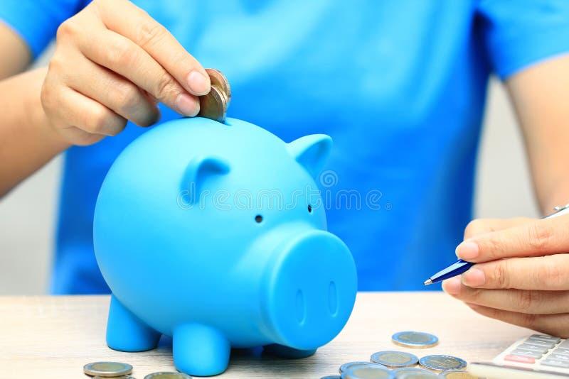 Kvinnahanden som sätter ett mynt in i spargrisen på naturlig grön bakgrund, affärsinvesteringen och räddningpengar för för royaltyfria bilder