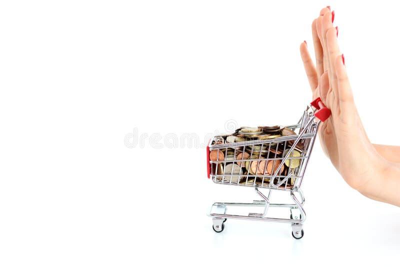 Kvinnahanden som skjuter en shoppingvagn, fyllde med pengar på vit bakgrund royaltyfria bilder