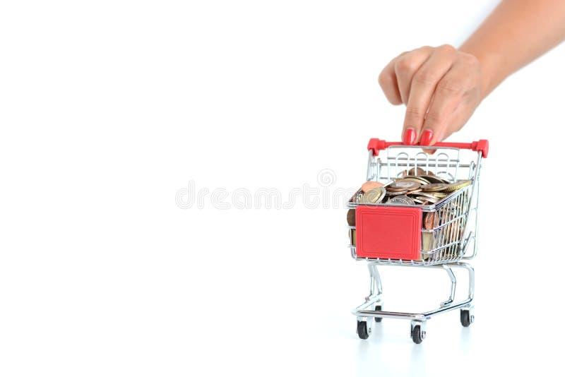 Kvinnahanden som skjuter en shoppingvagn, fyllde med pengar på vit bakgrund arkivbilder