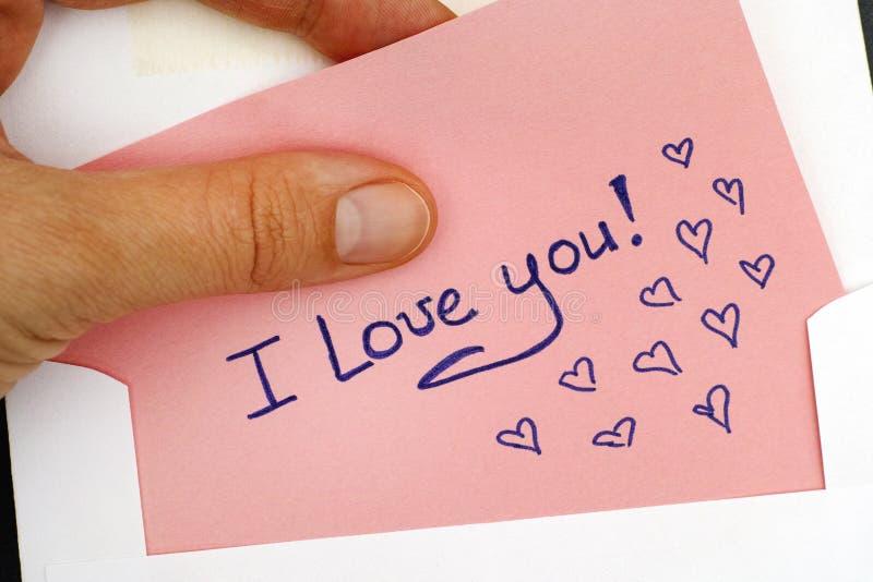 Kvinnahanden som ut tar bokstaven med text älskar jag, dig! från kuvert royaltyfri foto