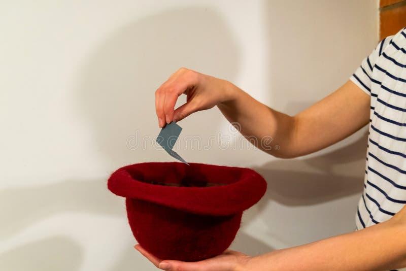 Kvinnahanden tar ett kort med ett namn från hatten arkivfoto