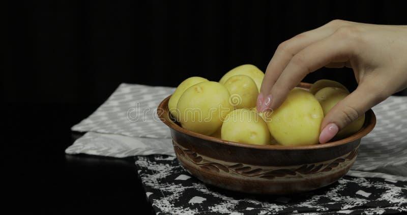 Kvinnahanden tar potatisar Tv?ttade nya r? potatisar arkivfoto