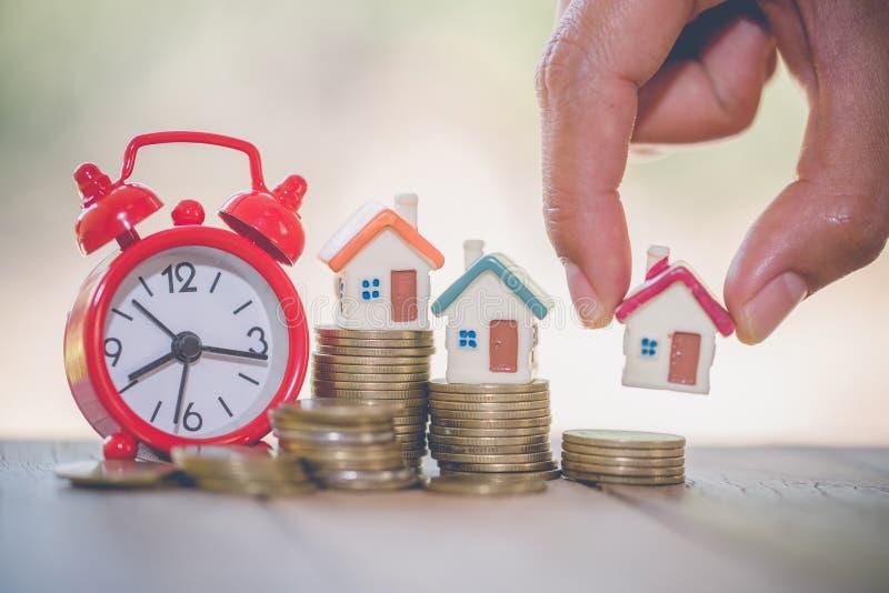 Kvinnahandhåll som en pålagd hem- modell buntmyntet med att växa i allmänheten parkerar, besparingpengar för köphus och lån till arkivbild