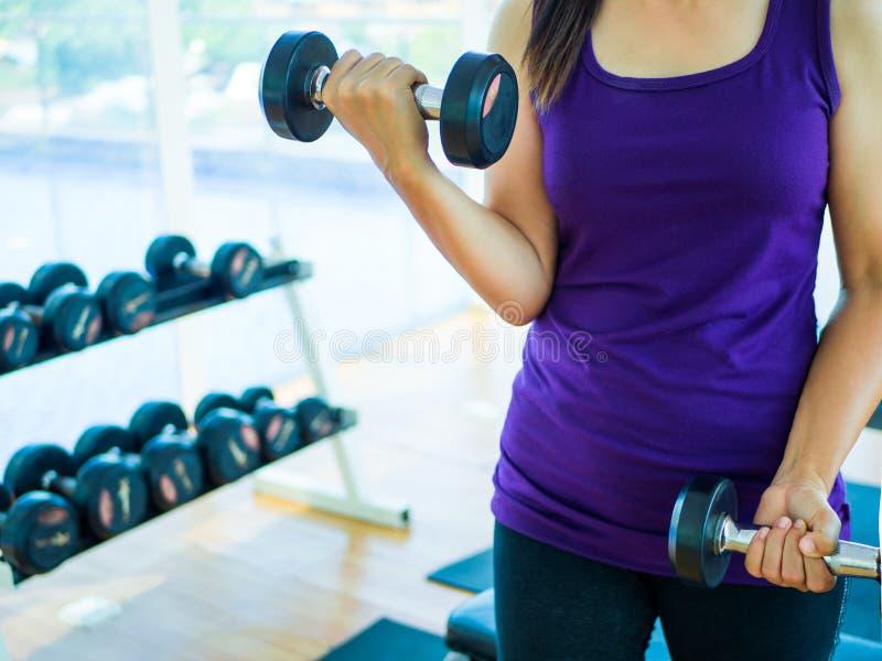 Kvinnahandlyftande hantel i gymnastiksal med konditionutrustningar i bakgrund royaltyfria bilder