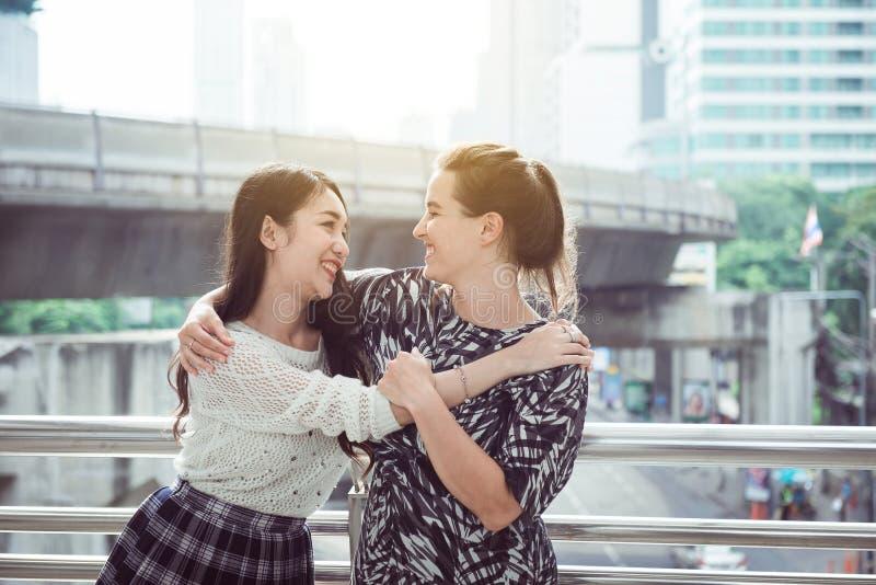 Kvinnahandmöte, lycklig hälsning av vän som två tillsammans kramar och ler arkivfoto