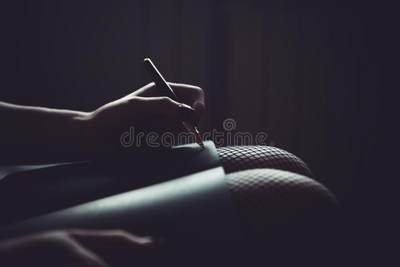 Kvinnahandstil i anteckningsbok på hennes knä flickahandstil med en penna i svart pappers- anteckningsbok isolated rear view whit royaltyfri foto