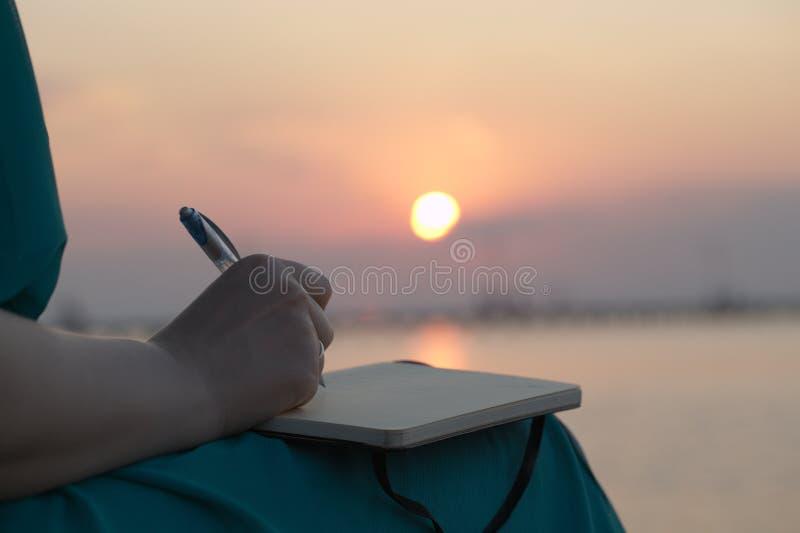 Kvinnahandstil i hennes dagbok på solnedgången royaltyfri fotografi