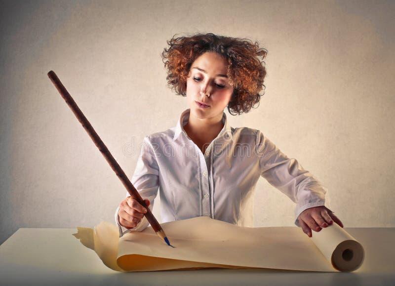 Kvinnahandstil med en enorm blyertspenna royaltyfri fotografi