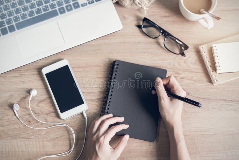Kvinnahandstil på anteckningsboken på arbetsplatsen arkivbilder