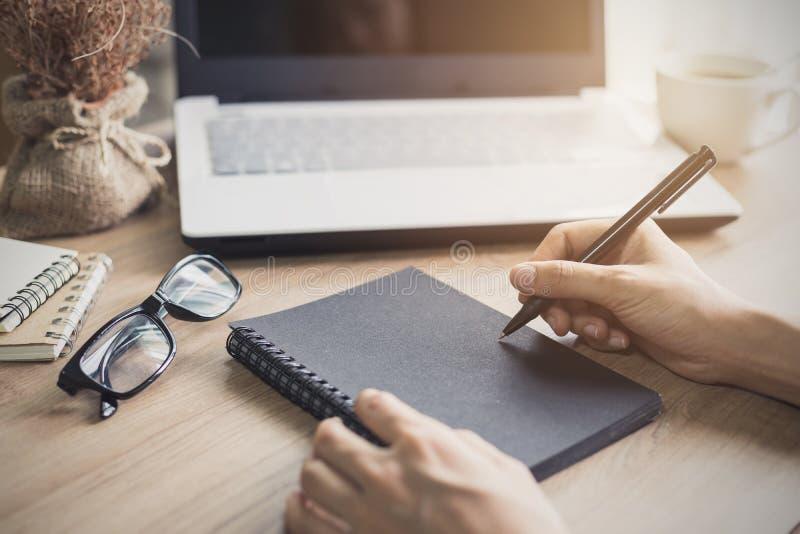Kvinnahandstil på anteckningsboken på arbetsplatsen royaltyfri fotografi