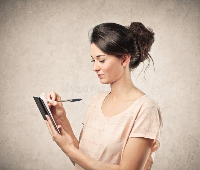 Kvinnahandstil på hennes anteckningsbok arkivfoto