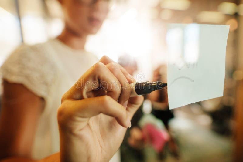 Kvinnahandstil på klibbig anmärkning under kontorsmöte fotografering för bildbyråer