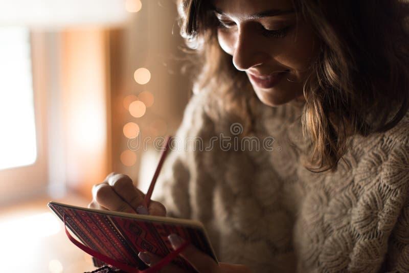 Kvinnahandstil på sketchbook arkivbild