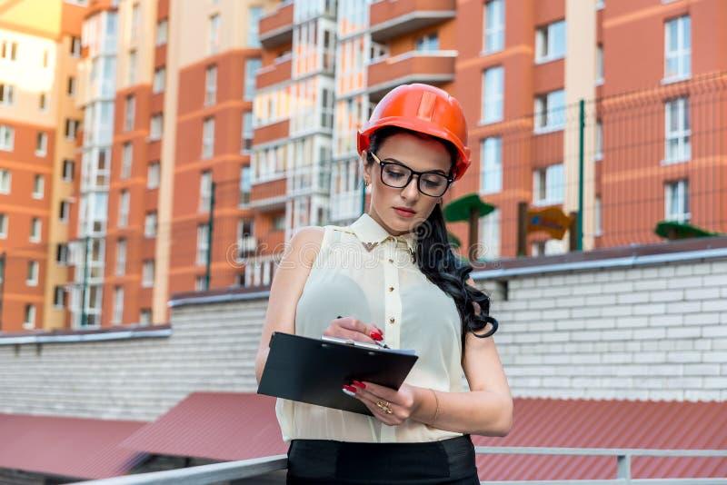Kvinnahandstil på skrivplattan på konstruktionsplats royaltyfri fotografi