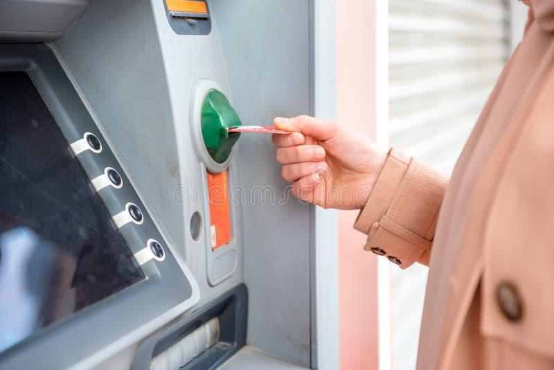 kvinnahandstund genom att använda ATM på gatan royaltyfri foto