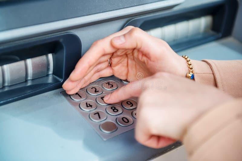 kvinnahandstund genom att anv?nda ATM p? gatan arkivfoton