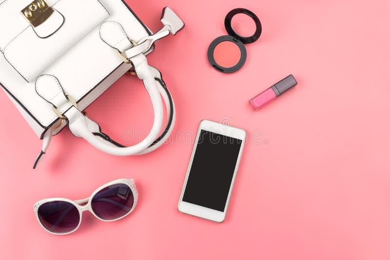 Kvinnahandväska med makeup och tillbehör som isoleras på rosa backg arkivfoton