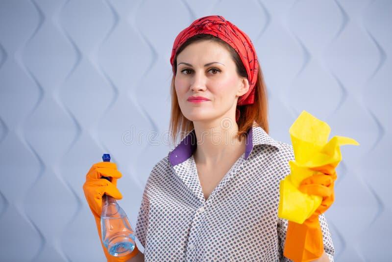 Kvinnahemmafru med den rengörande flasksprej och trasan i hand på blå bakgrund royaltyfria bilder