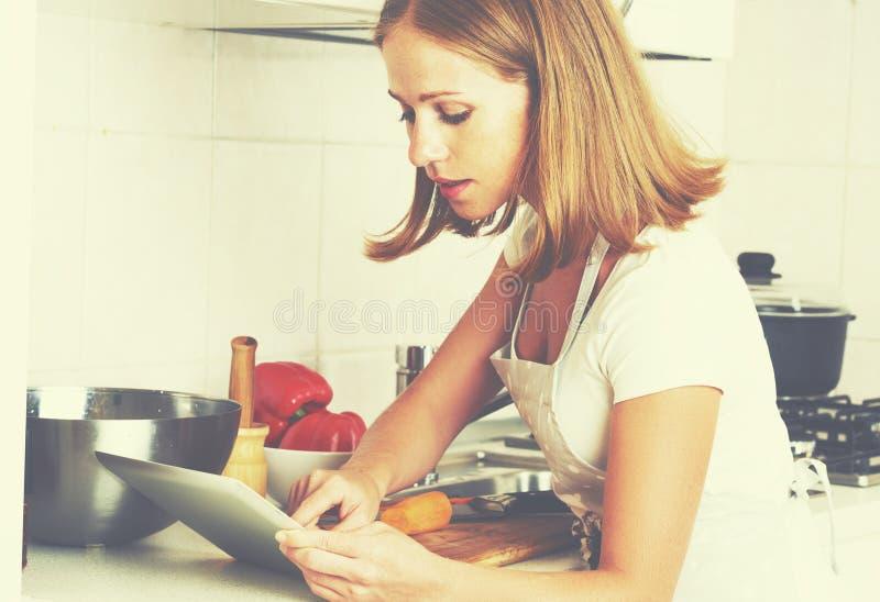Kvinnahemmafrun lagar mat mat ett recept från internet med en minnestavla royaltyfria foton