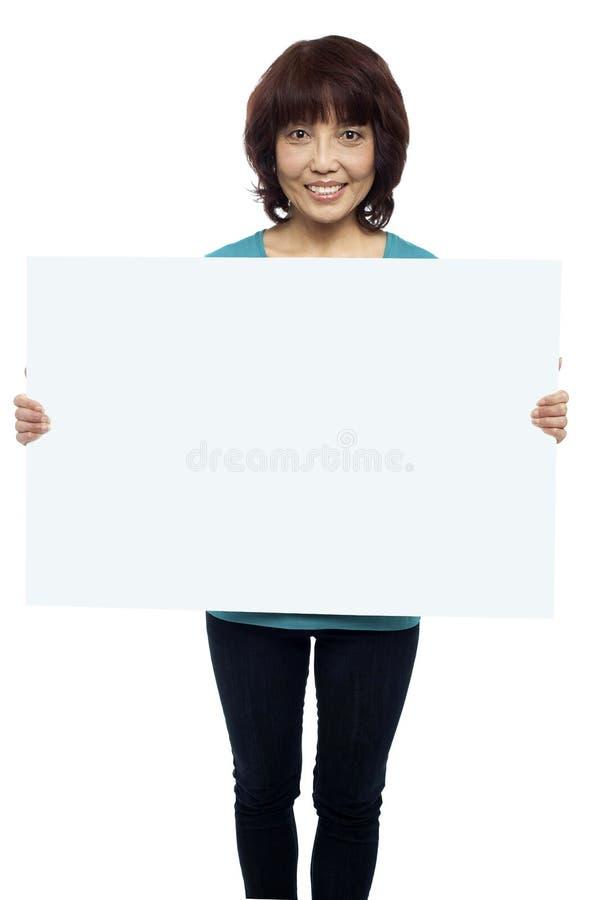 Kvinnaholdingaffischtavla, din annons här royaltyfri fotografi