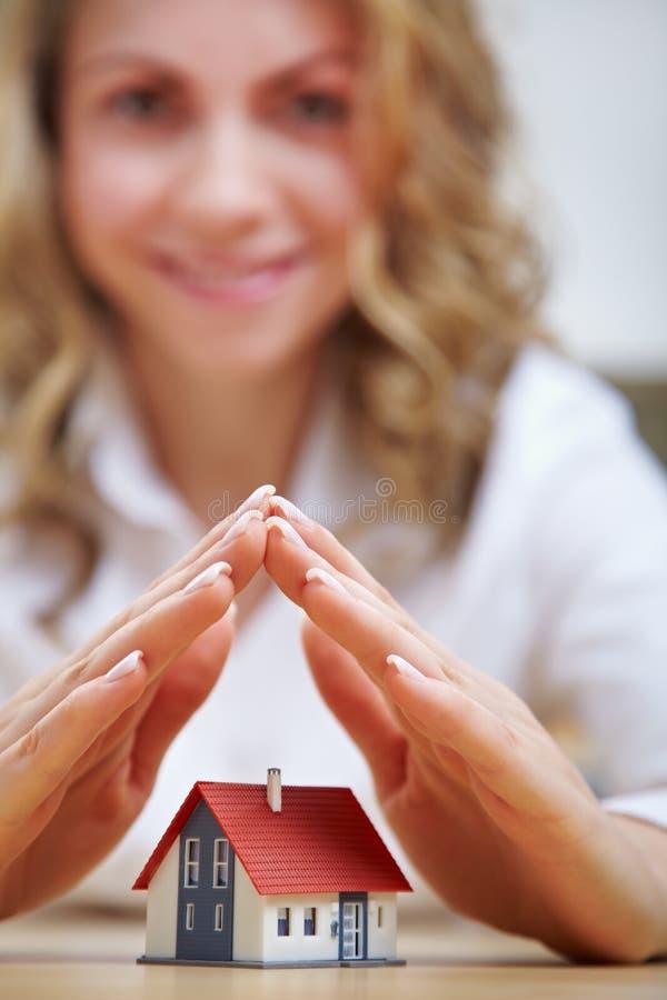 Kvinnaholdinghänder över hus royaltyfri foto